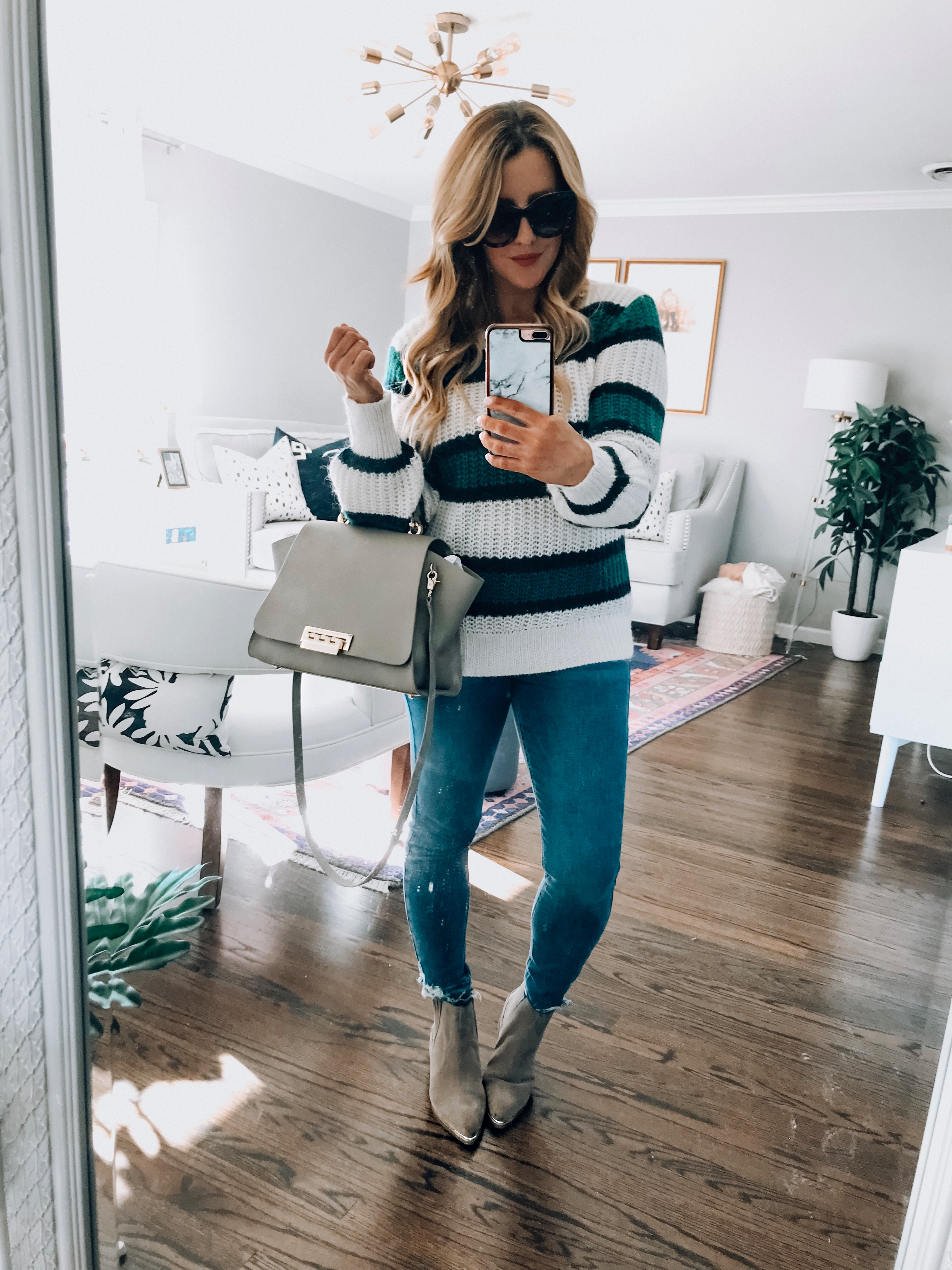 Best Striped Sweaters roundup featured by top US fashion blog, For the Love: image of a woman wearing an Abercrombie & Fitch striped sweater, TOPSHOP ripped hem jeans and Zac Posen Crossbody bag.