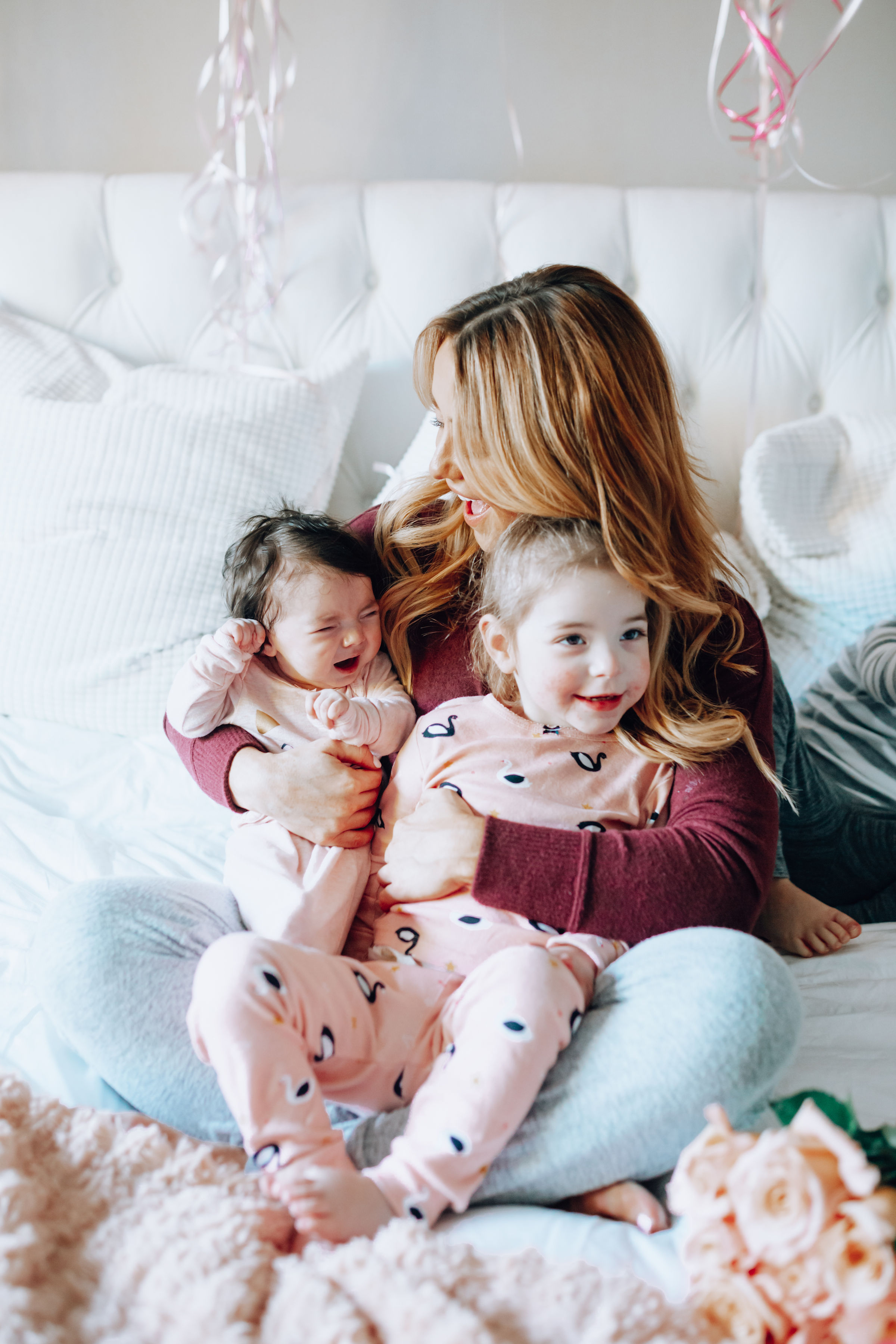 Top 7 Birthday Gifts for Yourself featured by top US life and style blog, For the Love: image of a mom and her 3 children in her bedroom having fun with balloons.