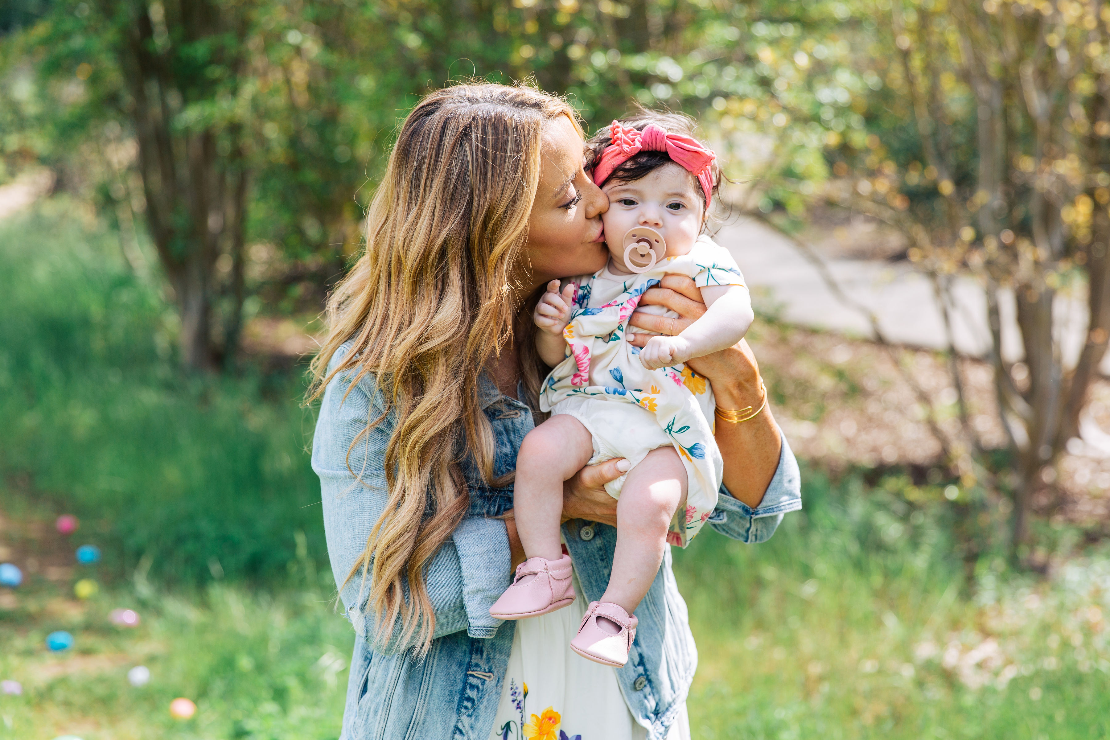 Easter traditions and cute Easter dresses featured by top US life and style, For the Love: image of a woman with her daughters wearing an Old Navy floral midi dress, Something Navy denim jacket and March Fisher snake print sandals